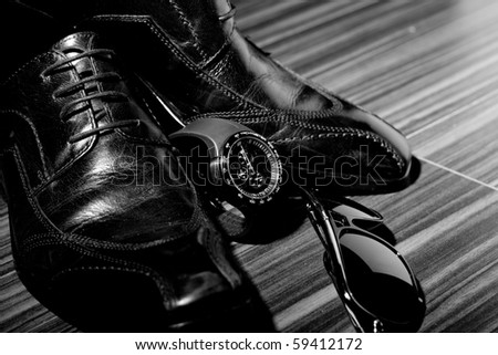 Dress shoes and a watch in the spotlight (focus on watch) - stock photo