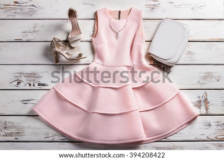 Dress with footwear and jewelry. Tailor-made clothes on shelf. Woman's clothing and accessories. Evening collection in lookbook. - stock photo