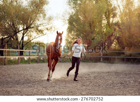 Dressage. Beautiful young woman running with her brown horse at countryside. - stock photo