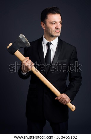 dressed man in studio shows an ax