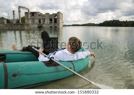 Dressed man lay over boat on lake shore