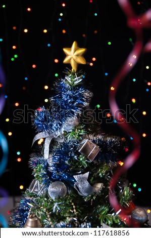 dressed up fur-tree with the star on top,streamers on a black background with colored lights