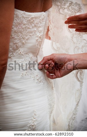 Dressing a bride - stock photo