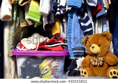 Dressing closet for kids with clothes arranged on hangers and teddy bears.Colorful wardrobe of newborn,kids, toddlers, babies full of all clothes.Many t-shirts,pants, shirts,blouses, onesie hanging - stock photo