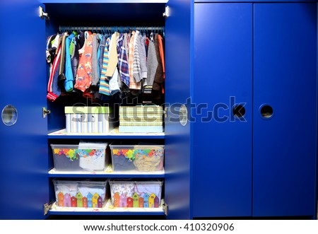 Dressing closet for kids with clothes arranged on hangers.Colorful wardrobe of newborn,kids, toddlers, babies full of all clothes.Many t-shirts,pants, shirts,blouses, onesie hanging - stock photo