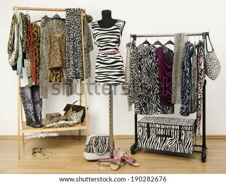 Dressing closet with animal print clothes arranged on hangers and a zebra print outfit on a mannequin. Colorful wardrobe with jungle pattern clothes and accessories. - stock photo