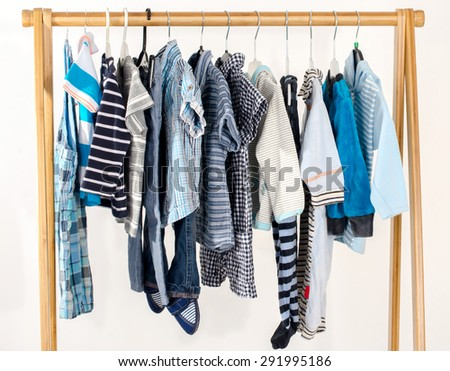 Dressing closet with clothes arranged on hangers.Blue and white wardrobe of newborn,kids, toddlers, babies full of all clothes.Many t-shirts,pants, shirts,blouses, onesie hanging - stock photo