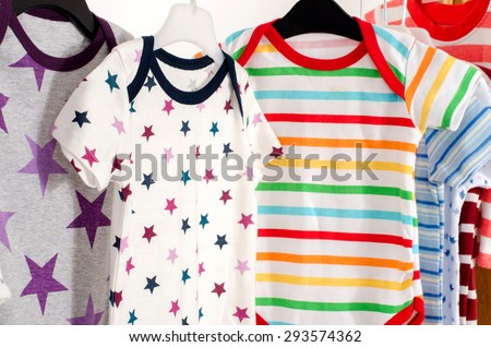 Dressing closet with clothes arranged on hangers.Colorful onesie of newborn,kids, toddlers, babies on a rack.Many colorful t-shirts, shirts,blouses, onesie hanging - stock photo