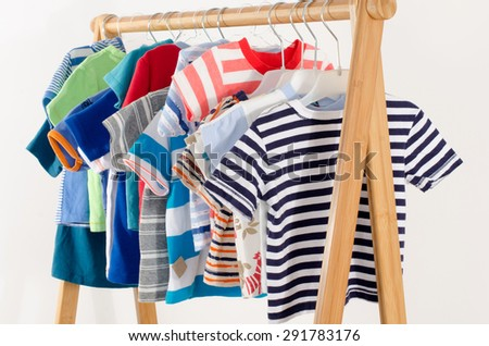 Dressing closet with clothes arranged on hangers.Colorful wardrobe of newborn,kids, toddlers, babies full of all clothes.Many t-shirts,pants, shirts,blouses, onesie hanging - stock photo