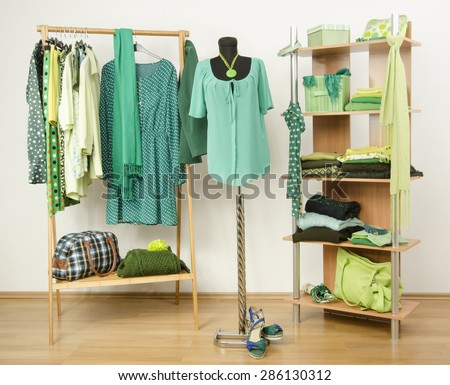 Dressing closet with green clothes arranged on hangers and shelf, outfit on a mannequin. Wardrobe full of all shades of green clothes and accessories. - stock photo