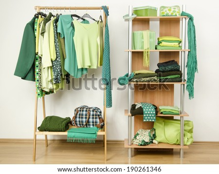 Dressing closet with green clothes arranged on hangers and shelf. Wardrobe full of all shades of green clothes and accessories. - stock photo