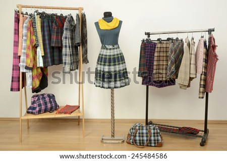 Dressing closet with plaid clothes arranged on hangers and an outfit on a mannequin. Colorful wardrobe with tartan clothes and accessories. - stock photo