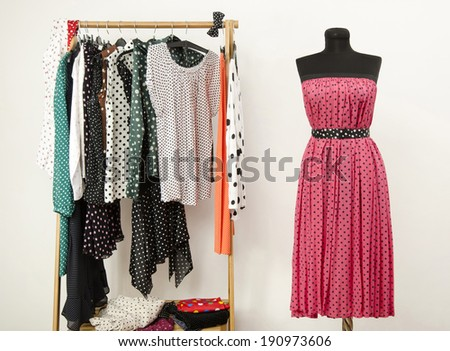 Dressing closet with polka dots clothes arranged on hangers and a pink dress on a mannequin. Colorful wardrobe with polka dots clothes and accessories.   - stock photo