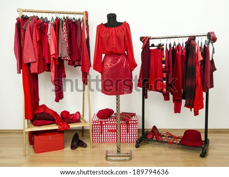 Dressing closet with red clothes arranged on hangers and an outfit on a mannequin. Wardrobe full of all shades of red clothes, shoes and accessories. - stock photo