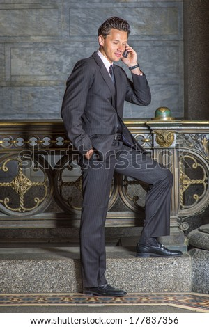 Dressing formally and standing by a railing a young businessman is smilingly talking on a mobile phone. / Talking on Phone  - stock photo