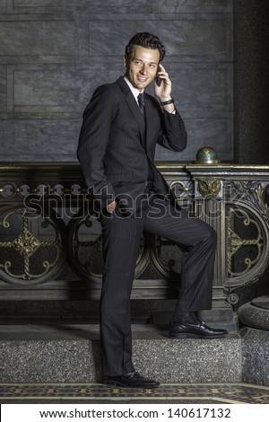 Dressing formally and standing by a railing a young businessman is smilingly talking on the phone.  - stock photo