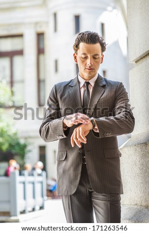 Dressing formally,  holding a watch in his wrist, a young businessman is standing outside an office building, looking down and checking time. / Time - stock photo