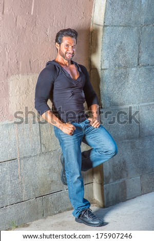 Dressing in a black sweater, blue jeans and leather shoes, a handsome, sexy, middle age guy with mustache and beard is leaning against the wall, smilingly looking at you. / Portrait of Middle Age Guy  - stock photo