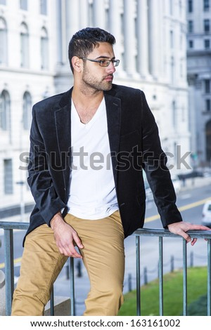 Dressing in a black woolen blazer, white underwear and dark yellow pants, wearing glasses, a young professional with bread and mustache is causally sitting by a railing, relaxing and thinking. - stock photo