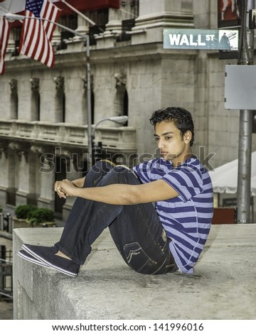 Dressing in a blue lines T shirt, a fashionable pants, and sitting on a stage by the street,  a young asian teenager is looking down and thinking/Thinking by Street  - stock photo