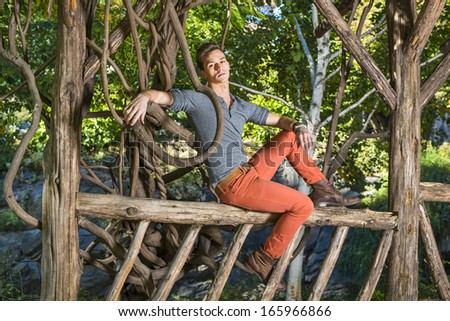 Dressing in a gray long sleeves with roll-tab Henley shirt,  red jeans and brown leather boot shoes, a young guy is sitting on a wooden fence and leaning on a rattan, relaxing outside.