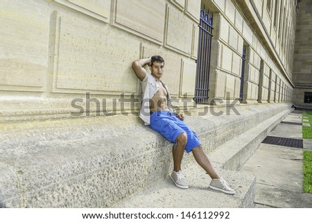 Dressing in a iron short sleeve shirt, blue shorts and sneakers , a young attractive guy is sitting against a pattern wall and relaxing. /Relaxing Outside