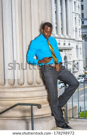 Dressing in a light blue shirt, gray pants, leather shoes,  a pattern tie, a young black businessman is standing outside an office building, checking messages on his mobile phone. / Text Outside - stock photo