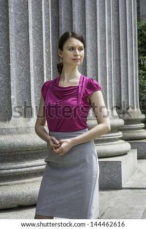 Dressing in a purple top and gray skirt, a young beautiful businesswoman is standing by columns of  the office, thoughtfully looking away./Portrait of Young Businesswoman