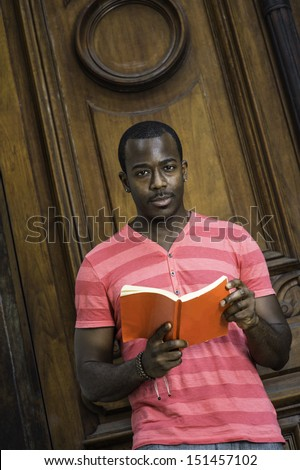 Dressing in a red, pink lines T shirt, wearing a bracelet, a young black guy is reading a red book outside. / Black Guy and Red Book  - stock photo
