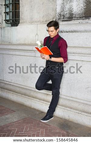 Dressing in a red shirt, a black vest, black jeans and a black tie, a young handsome guy is reading a red book with a white rose. / Reading Outside