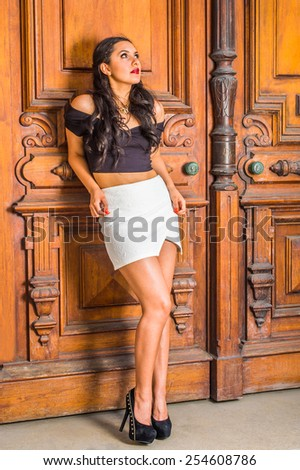 Dressing in black, short sleeve top, white short wrap skirt, high heals, a young student is leaning on library door, looking up, thinking. Concept of teenagers questioning life, self esteem. - stock photo