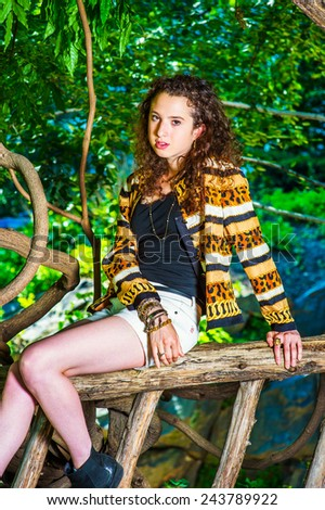 Dressing in black top, patterned fashion jacket, short pants, chunky chain bracelet, a teenager girl with curly long hair sitting in wooden area, looking at you. Woman Fashion in Location.   - stock photo
