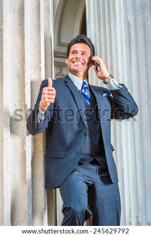 Dressing in dark blue three piece suit, necktie, a handsome, sexy, middle age businessman is standing outside office, looking up, smiling, giving thumbs up, making a phone call on his mobile phone. - stock photo