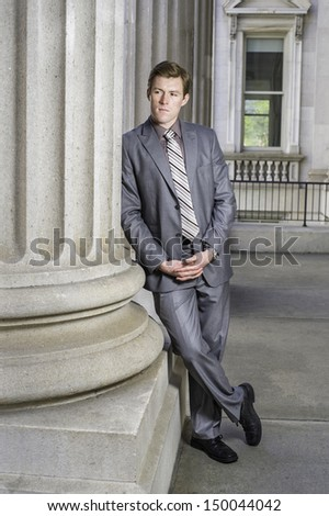 Dressing in gray suit and a pattern tie, a young businessman is standing by a column outside a office building and taking a break. / Relaxing Outside - stock photo