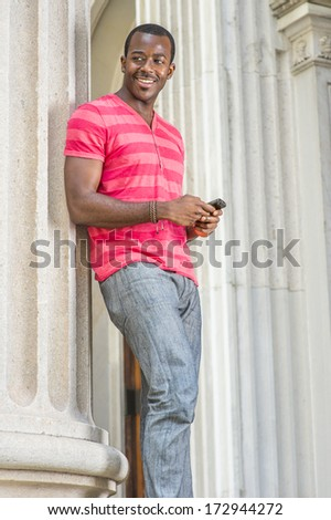 Dressing in red, pink stripe Henley V Neck T shirt,  gray pants, wearing a bracelet, a young black guy is standing by a column, checking messages on his smart phone. / Text - stock photo