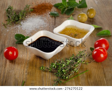 Dressing ingredients on a rustic background. Olive oil, balsamic vinegar, herbs, salt and pepper. Selective focus - stock photo