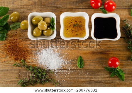 Dressing ingredients on  rustic wooden background. Olive oil, balsamic vinegar, herbs, salt and pepper. Top view - stock photo