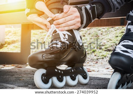 dressing roller skates for skating. Focus on hands - stock photo