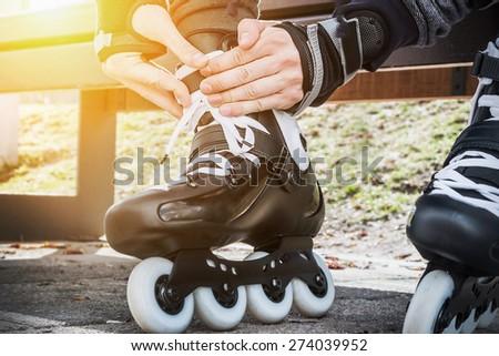 dressing roller skates for skating. Focus on hands - stock photo