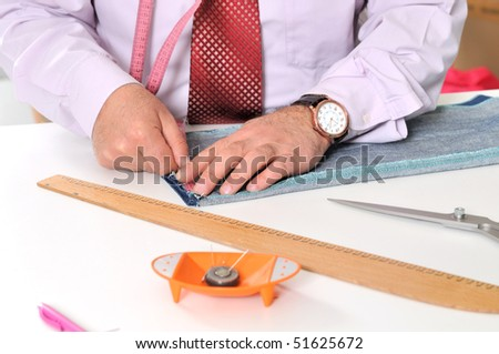 Dressmaker cutting fabric - A series of TAILOR related images. - stock photo