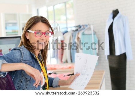 Dressmaker designing clothes pattern on paper - stock photo