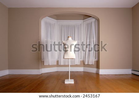 Dressmaker's mannequin in an empty room - stock photo