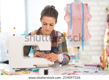 Dressmaker woman working with sewing machine - stock photo