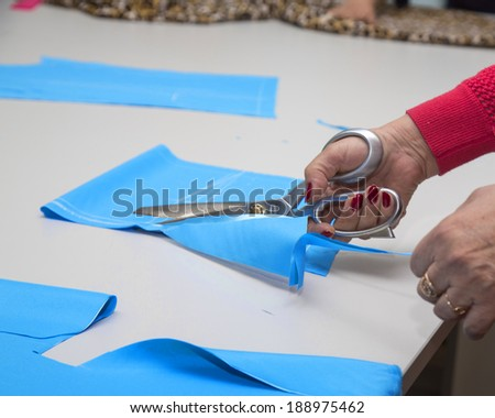 dressmakers cutting blue fabric.Close up