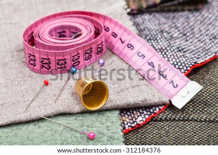 dressmaking still life - pink measure tape, pins, thimble on textile - stock photo