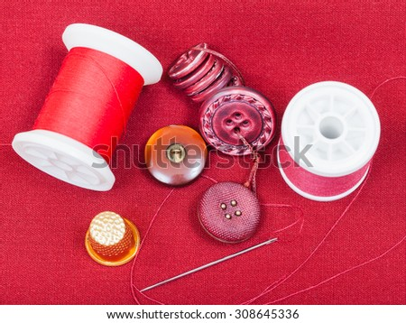 dressmaking still life - top view of bobbins with sewing thread, buttons, thimble, needle on red tissue - stock photo