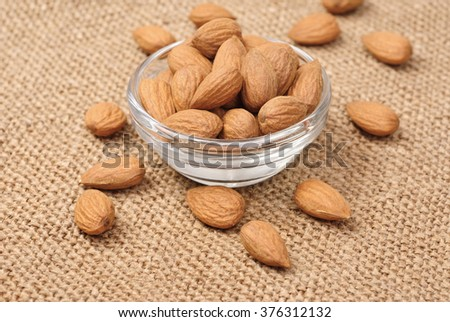 Dried almonds on glass bowl on canvas background - stock photo