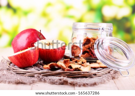 Dried apples in glass jar, on   bright background - stock photo