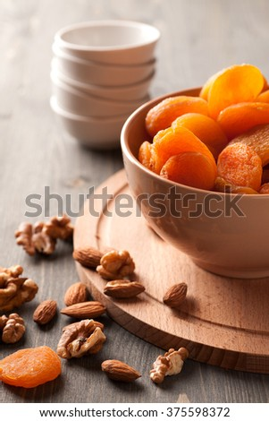 Dried apricots and nuts in a bowl on wooden table with empty dishies in the background, selective focus, vertical - stock photo