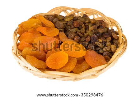 Dried apricots and raisins in wicker basket isolated on white background - stock photo